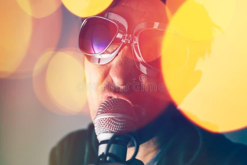 Alternativet vaggar sjungande sång för musiksångare in i mikrofonen arkivbild