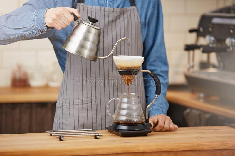 Alternativt kaffe för bartenderdanande genom att använda den manuella droppandebryggaren, hällande vatten arkivbild