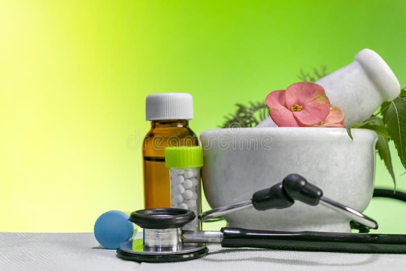 Alternatywnej medycyny pojęcie – Homeopatyczni Leczniczy ziele z tłuczkiem z stetoskopem wraz z butelką pigułki i moździerzem zdjęcie stock