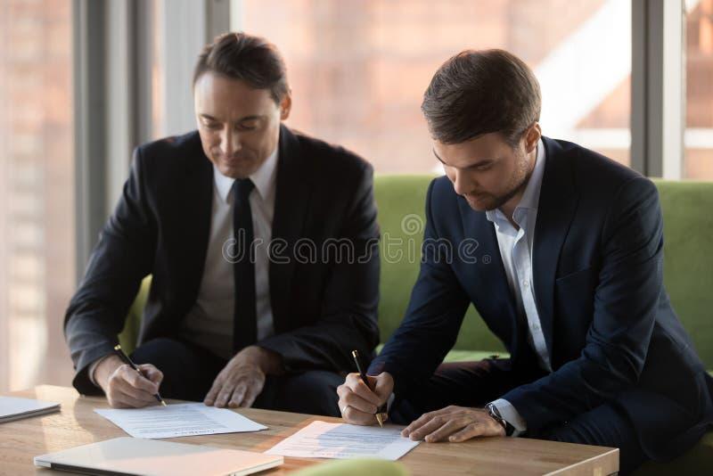 Alterte erfolgreiche Mitte zwei die Geschäftsmänner in den Klagen Verträge unterzeichnend lizenzfreie stockbilder