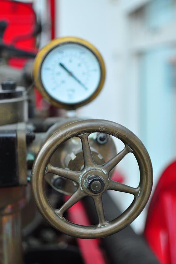 Altes antikes Weinlesefeuerlöschpumpemanometer und -rad lizenzfreies stockbild