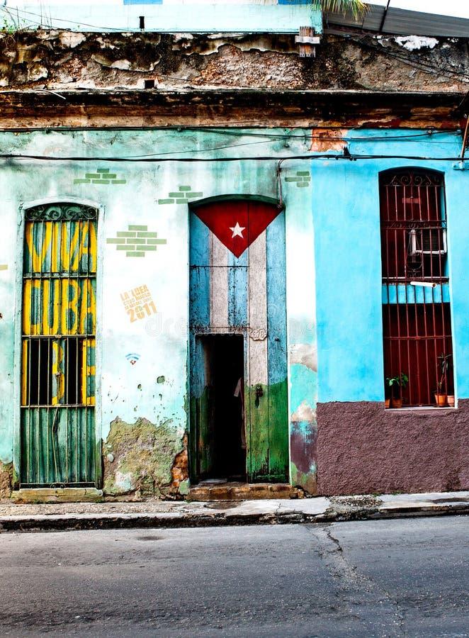Altes armseliges Haus in zentralem Havana malte mit der kubanischen Flagge a stockfoto