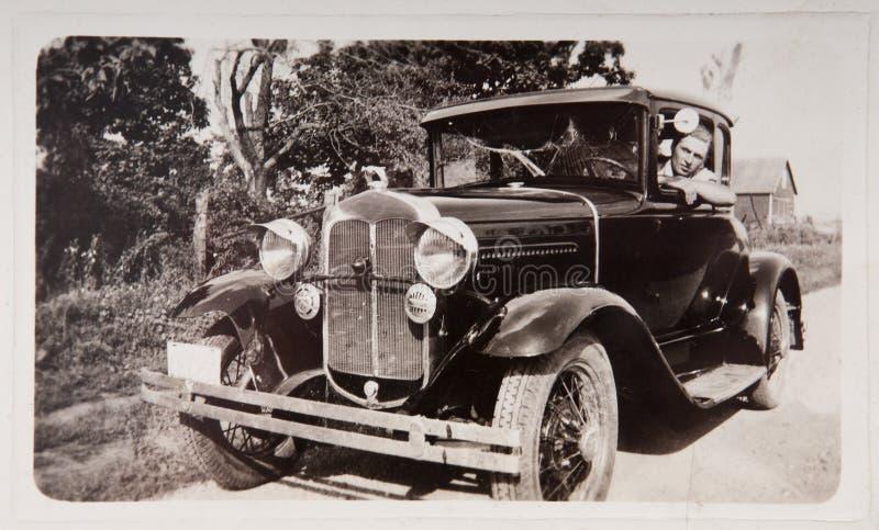 Altes Auto des Weinlese-Fotographien-junger Mann-Laufwerk-Baumuster-T stockfotografie