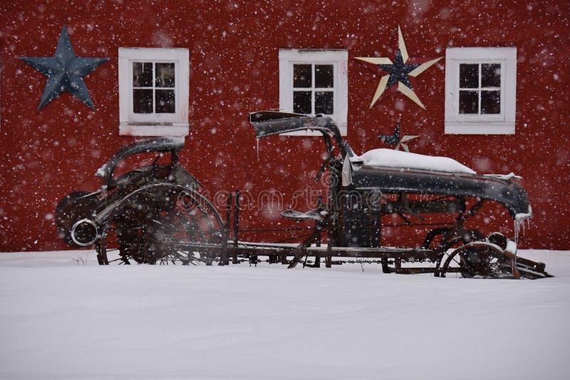 Altes Auto gegen rote Scheune im Winter lizenzfreie stockfotografie