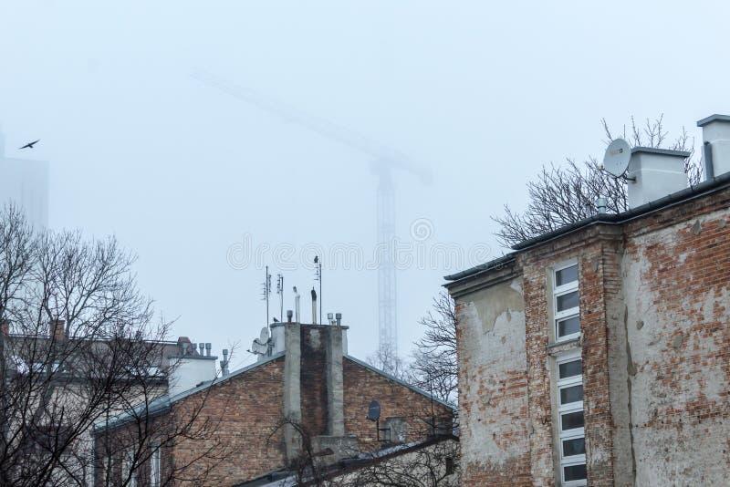 Altes Backsteinhaus und Kran im Nebel lizenzfreies stockfoto