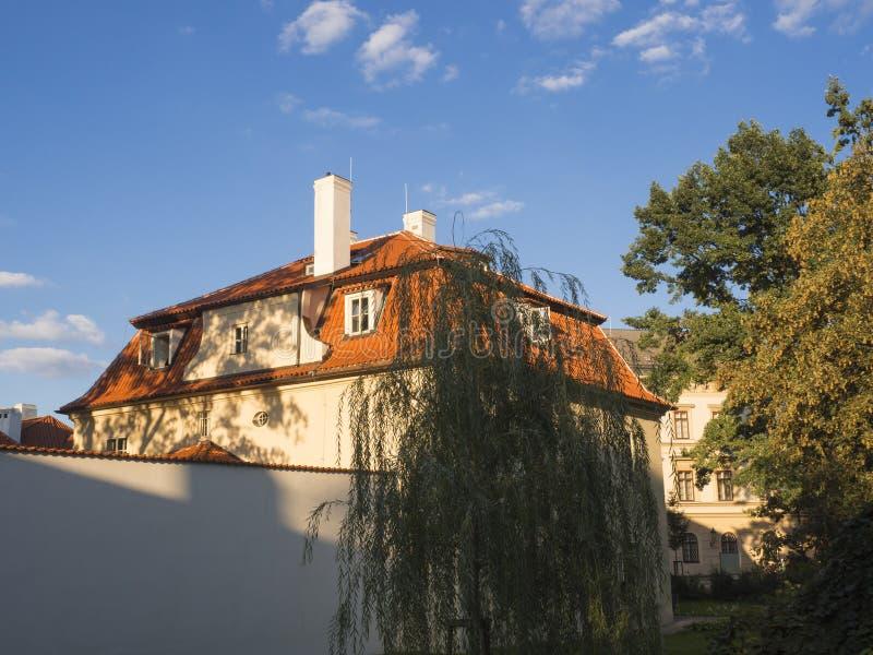 Altes barockes Haus Prags bei Kampa mit rotem Dach und weiße Umfassungswand, offenes Fenster im goldenen Stundenlicht, Bäume und stockbilder