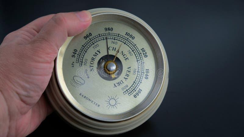 Altes Barometer in der Hand auf schwarzem Hintergrund lizenzfreie stockfotos