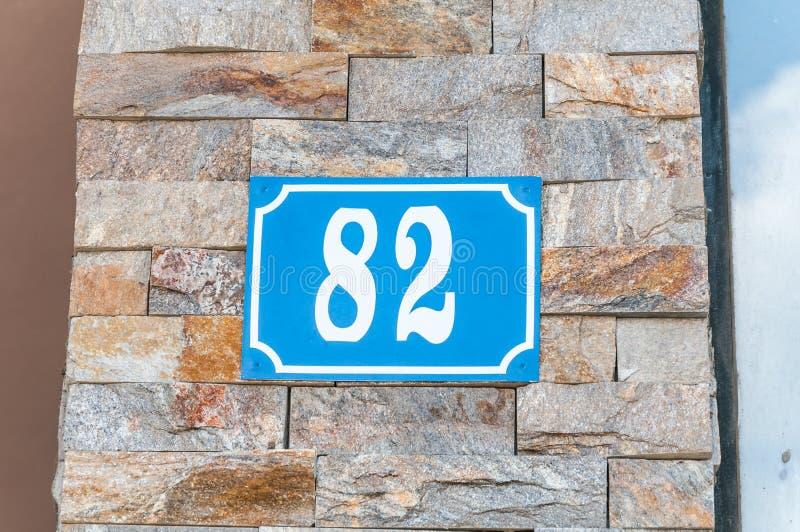 Altes blaues Weinlesehaus Adreßmetallplattenzahl 82 auf der dekorativen Ziegelsteinfassade der Wohngebäude-Außenwand auf dem s lizenzfreies stockbild