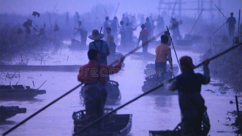 Altes Boot der chinesischen Mannreihen durch die Anwendung des langen Stockes yunnan China stockfotos