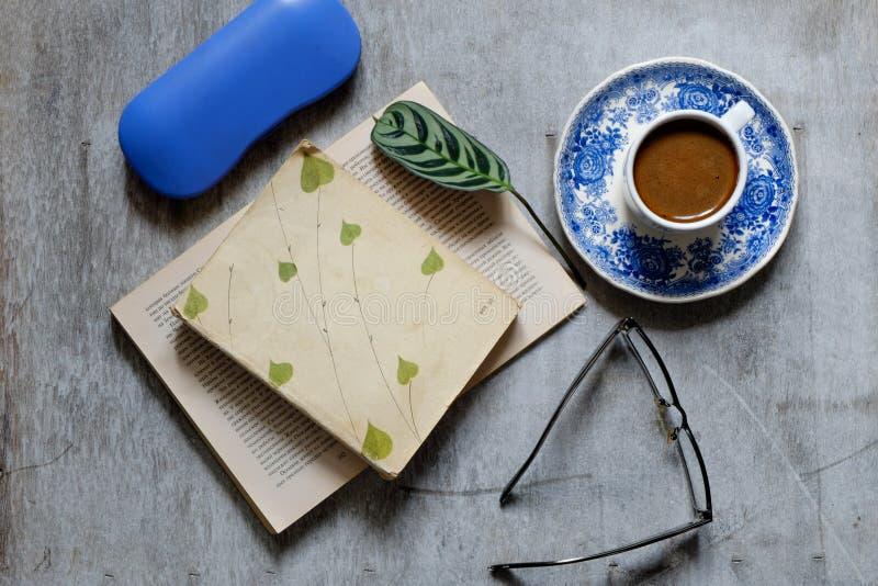 Altes Buch, Gläser, Tasse Kaffee und ein Umschlag auf dem Tisch Weinlese-noch Leben stockbilder
