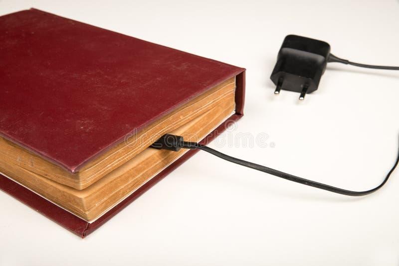 Altes Buch mit einem Batterieaufladungskabel stockfotografie