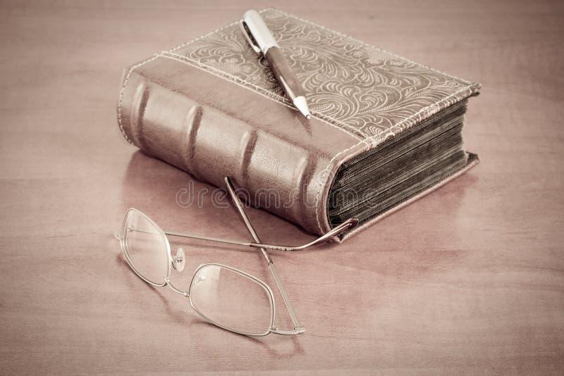 Altes Buch mit Lesegläsern und -feder lizenzfreie stockbilder