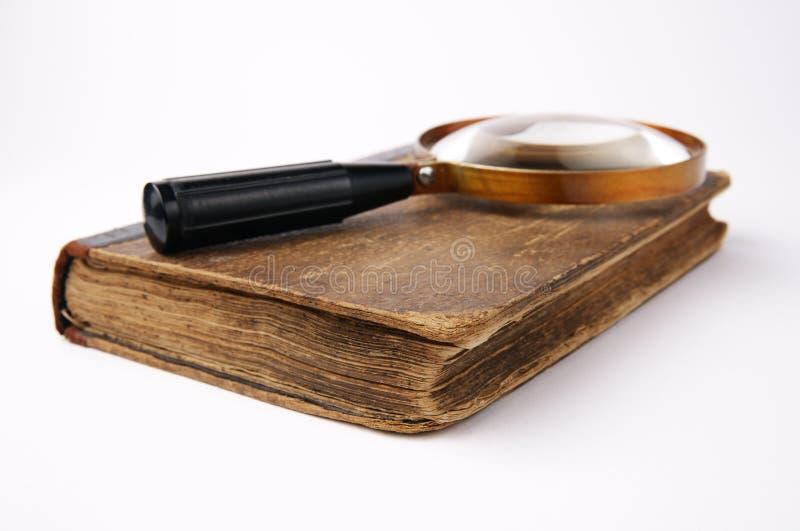 Altes Buch mit Lupe auf weißem Hintergrund stockfotografie