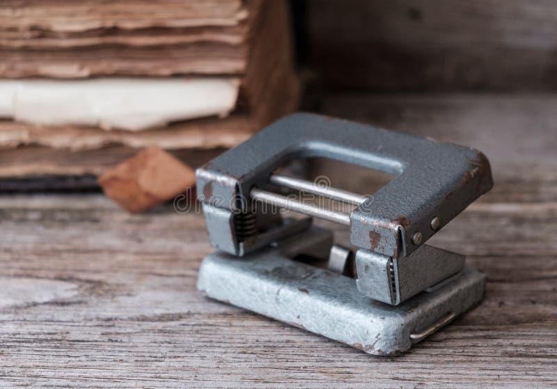 Altes Buch und alter Lochdurchschlag auf dem Tisch lizenzfreies stockfoto