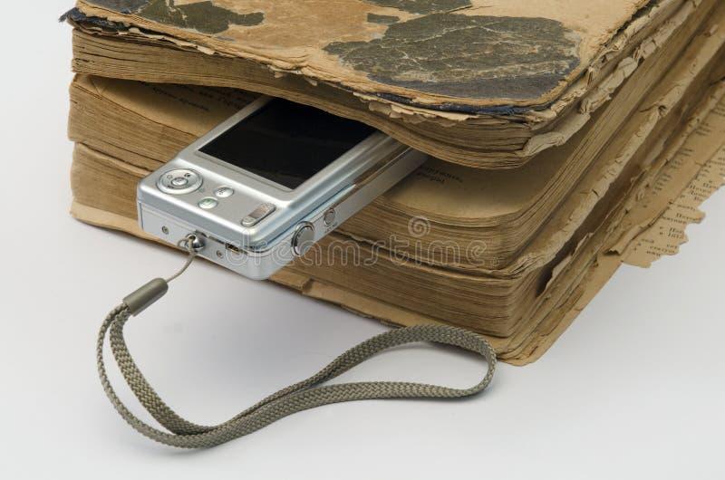 Altes Buch und eine Digitalkamera lizenzfreie stockfotografie