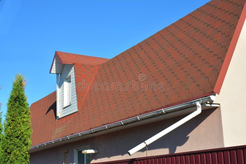 Altes Dach Asphalt Shingles mit Moos Regen-Gossen-Rohrleitung mit Downspout-Rohr und Dachboden-Mansarden-Fenster stockfotos