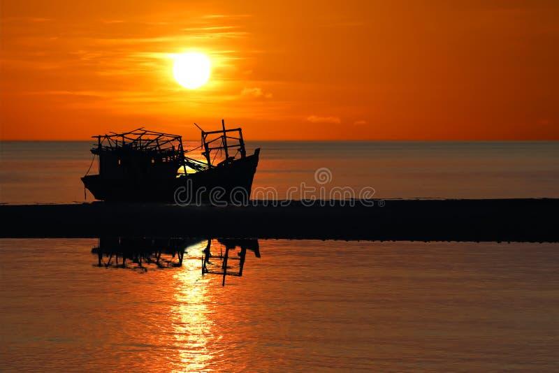 Altes defektes Boot verlassen auf dem Strand bei Sonnenuntergang lizenzfreie stockfotografie