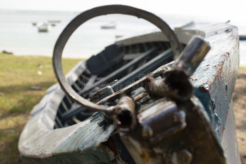 Altes defektes rostiges Boot neben dem Meer-bacground lizenzfreies stockbild