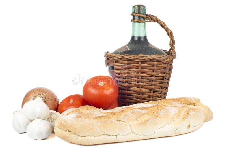 Altes Dekantiergefäß Rotwein mit frischem Brot, Tomaten, Knoblauch und Zwiebel. lizenzfreie stockfotos