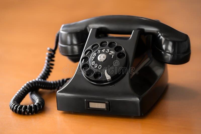 Altes Drehskalatelefon auf hölzernem Schreibtisch stockfoto