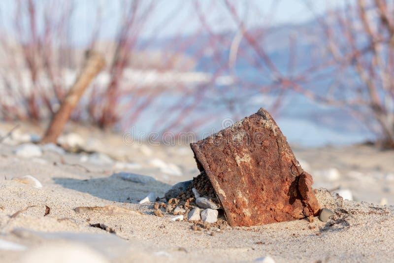 Altes eingemachtes links durch einen Mann auf dem Sandstrand verrostete Blechdose von unterhalb der Konserven E lizenzfreies stockfoto