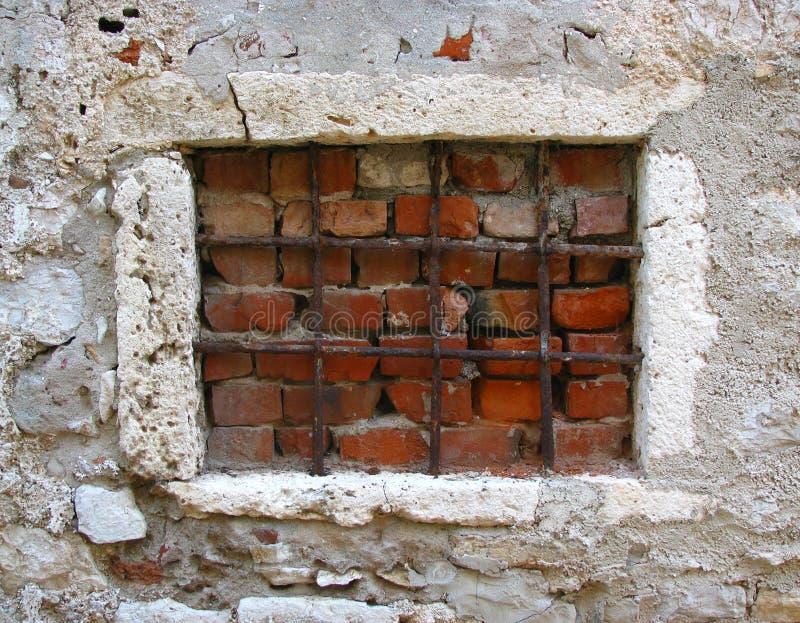 Altes Fenster geblockt mit Gittern und Ziegelsteinen lizenzfreies stockbild