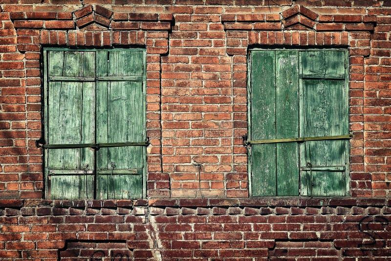 Altes Fenster mit geschlossenen Fensterläden auf einer Backsteinmauer stockfotografie