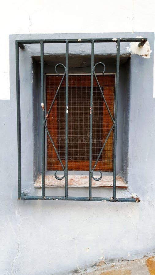 Altes Fenster mit Sicherheitsbars, Stahlgrill stockfoto