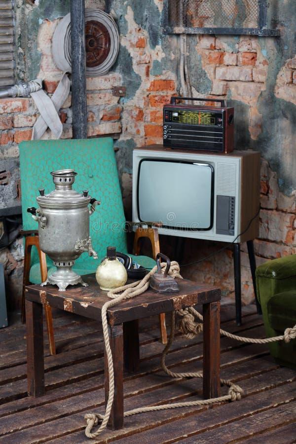 Altes Fernsehen, Radio und Holztisch mit Samowar lizenzfreie stockbilder