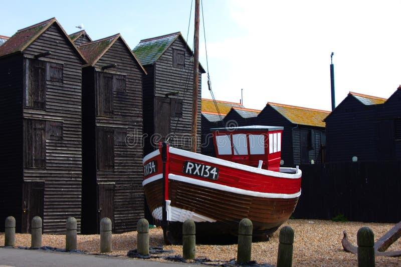 Altes Fischerboot auf dem Strand von Hastings mit Fischerhütten im Hintergrund lizenzfreie stockbilder