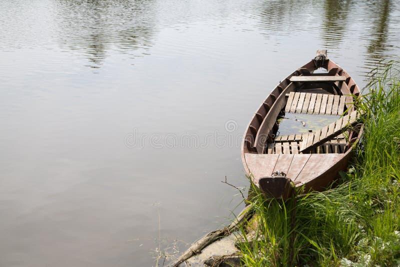 Altes Fischerboot im Fluss: Trauerhintergrund der Weinlese stockfoto