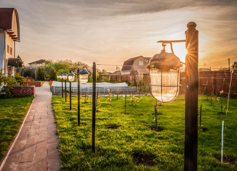 Altes Gartenlicht mit wasserdichter Abdeckung im Sonnenuntergang strahlt aus Plan des Plans stockfotografie