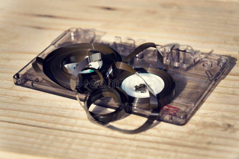 Altes gebrochenes abgewickeltes Magnetband für Tonaufzeichnungen der kompakten Kassette verwirrte oben auf hölzernem Hintergrund stockfotos