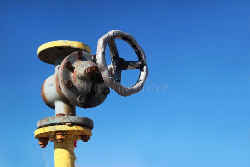 Altes gelbes Gasrohr mit Ventil auf Hintergrund des blauen Himmels lizenzfreie stockfotos