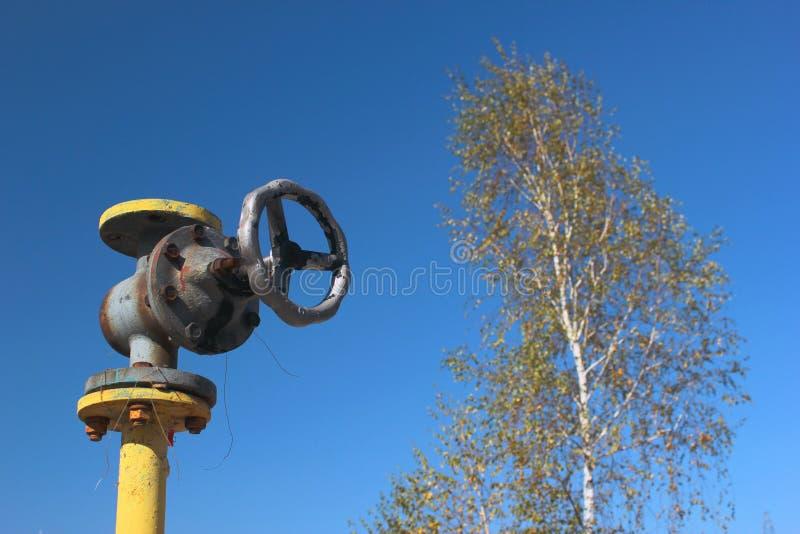 Altes gelbes Gasrohr mit Ventil auf Hintergrund des blauen Himmels stockfotografie