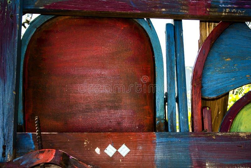 Altes gemalt u. befleckten Holzstühle gemacht in einen bunten Zaun stockfotografie