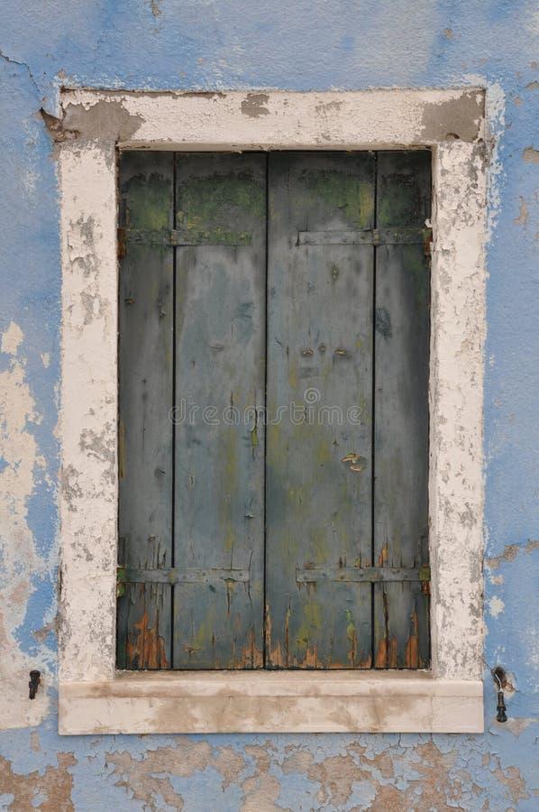 Altes geschlossenes Fenster mit Fensterladen auf blauer Wand stockfotografie