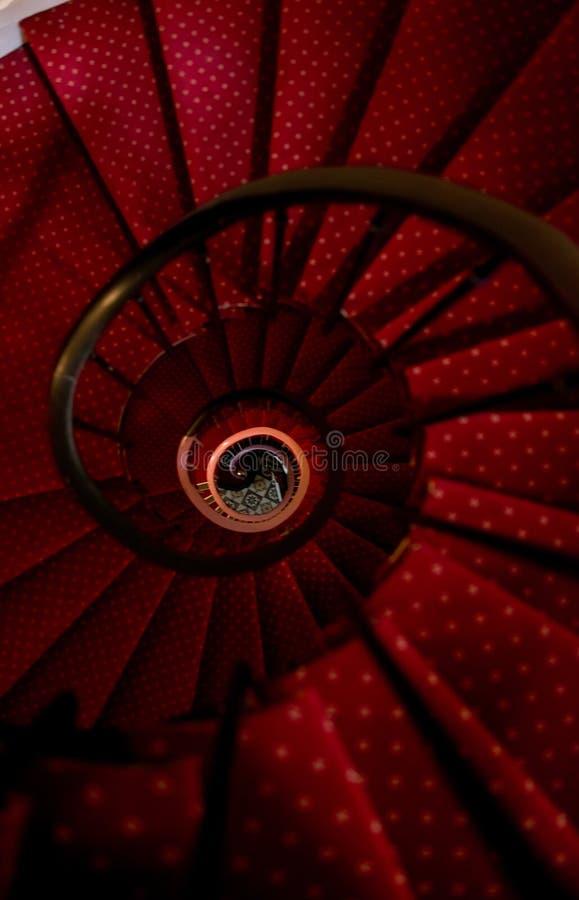 Altes gewundenes Treppenhaus des roten Teppichs lizenzfreie stockbilder