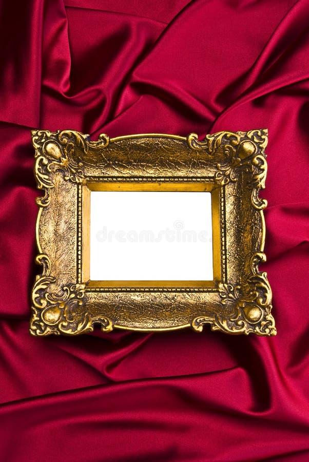 Altes Goldfeld auf rotem Satin stockbild