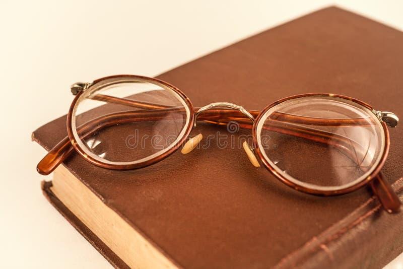 Altes grandmother& x27; s-Gläser und ein verfallenes Buch lizenzfreie stockfotografie