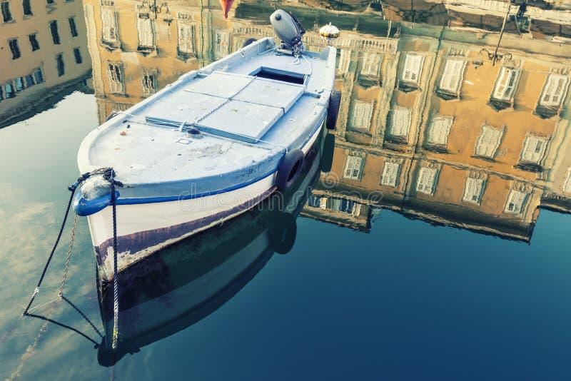 Altes hölzernes Boot, Himmel und altes historisches und Gebäude mit Reflexion auf blauem Wasser lizenzfreies stockbild