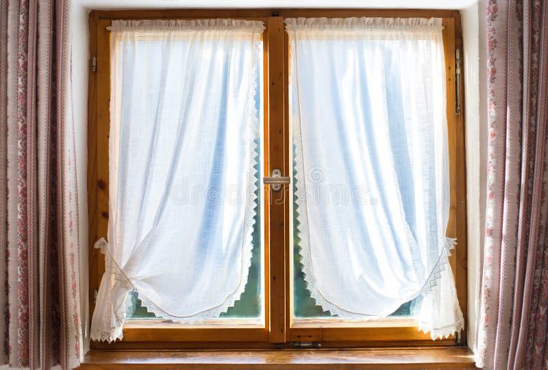 Altes hölzernes Fenster mit weißen Vorhängen stockbild
