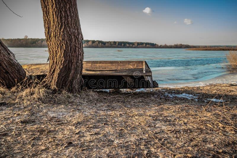 Altes hölzernes Fischerboot auf der Flussbank, welche die Navigationsjahreszeit erwartet stockbilder