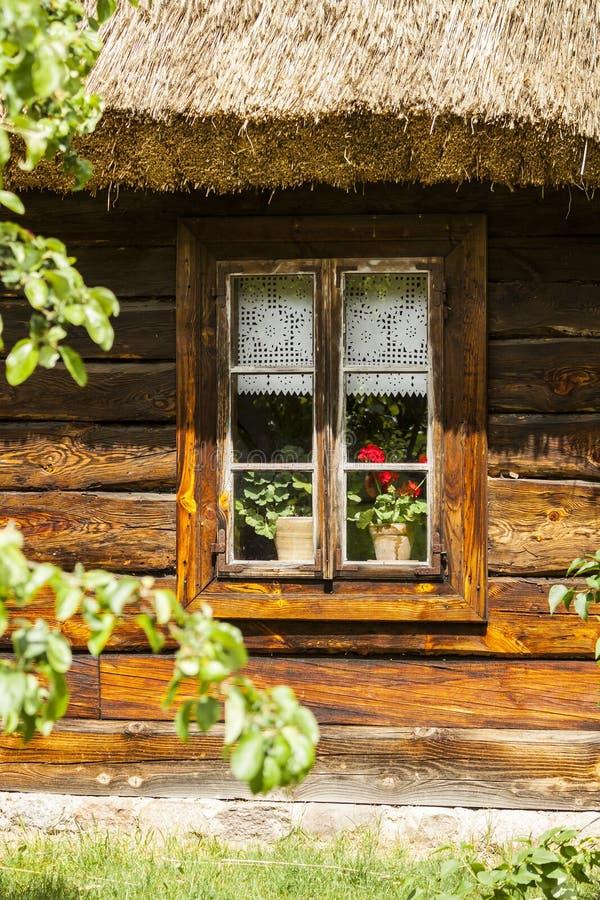 Altes hölzernes Haus Blühende Blumen auf Fenster lizenzfreie stockbilder