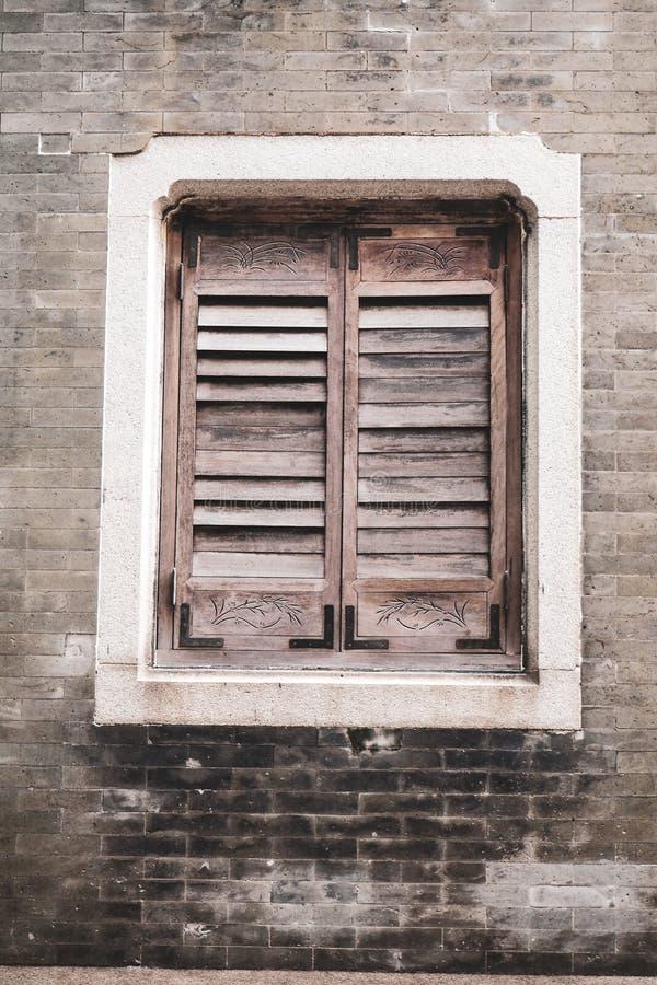 Altes hölzernes Jalousien-Fenster auf Backsteinmauer Alter rustikaler Ziegelsteinhintergrund der vertikalen Art stockfoto