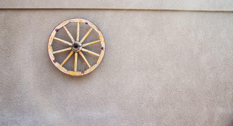 Altes hölzernes Pferdwagenrad auf der Wand lizenzfreie stockbilder