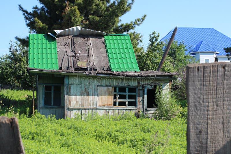 Altes hölzernes ruiniertes Haus verlassen im Gras mit einem schönen Muster auf dem Fenster lizenzfreie stockfotos