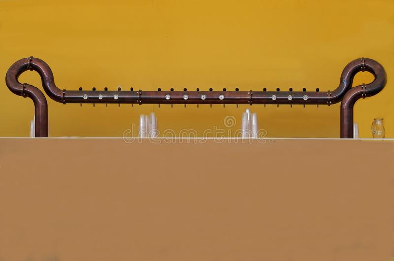 Altes HahnFassbiersystem gemacht vom Kupfer und vom Messing auf einfachem gelbem und braunem Hintergrund lizenzfreie stockbilder