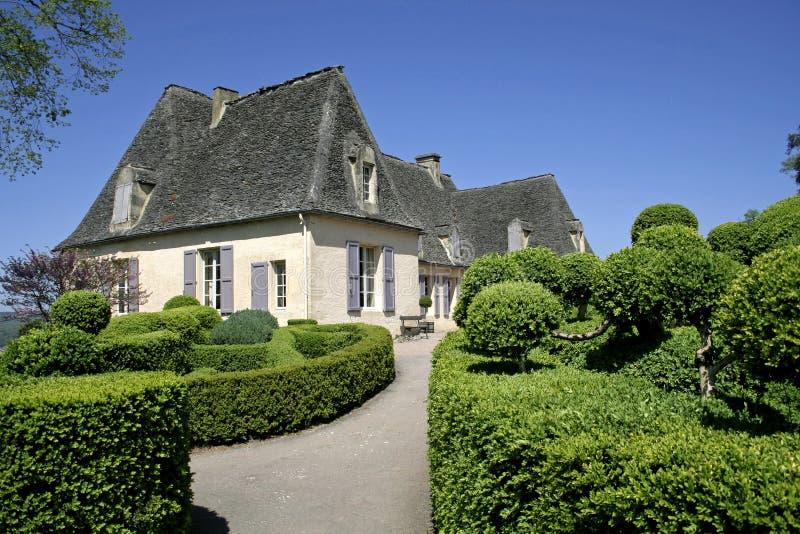 Altes Haus in landschaftlich verschönertem Garten lizenzfreie stockfotos