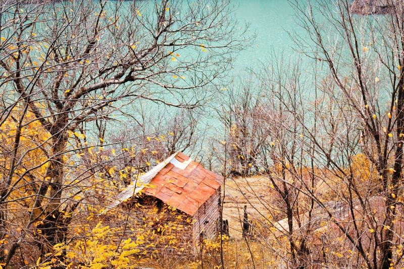 Altes Haus nahe dem See, umgeben durch Herbstbäume, Jagdhäuschen im Wald lizenzfreie stockfotos